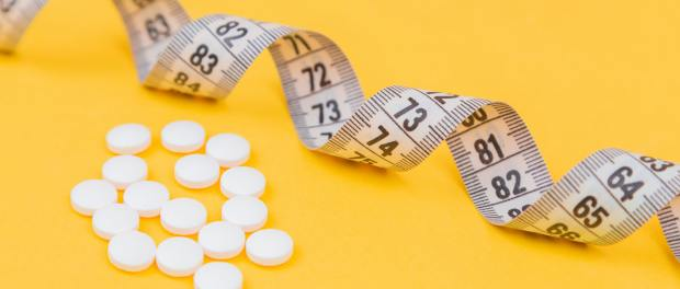 Pills and measuring tape on yellow background.
