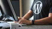 Man on computer with Wordpress logo on his tshirt