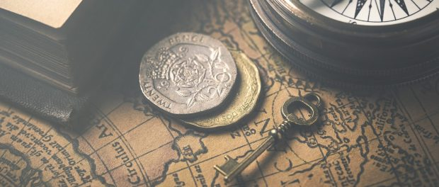 A small key next to loose change on a map.