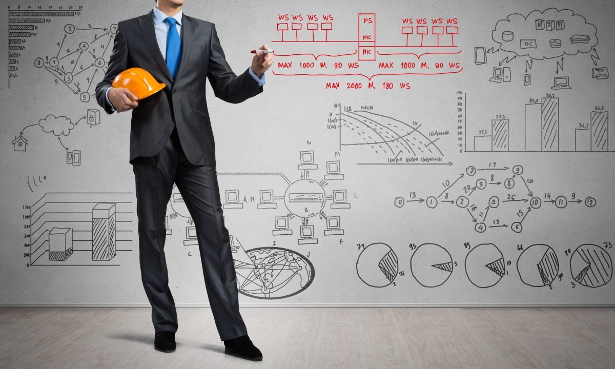 imagem de homem de terno engenheiro de produção segurando capacete e escrevendo em quadro com gráficos
