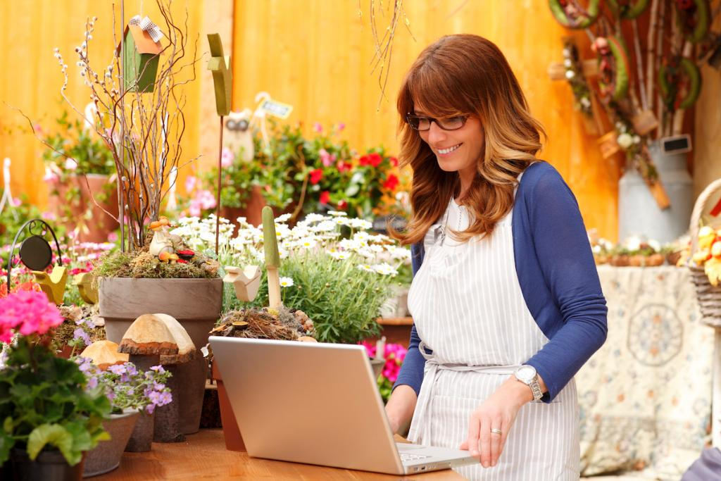 Flowershop owner smiles at a laptop, surrounded by plants