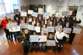 Year 4 pupils at St Wilfrid's C of E Primary School show off their framed artwork for Manchester Airport Christmas card