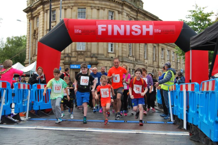 Parents and their children setting off at the Big Stockport Run & Family Fun Run