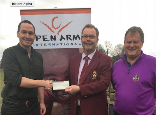 Roger Souter past captain at Bramall Park GC presents a cheque to Open Arms International