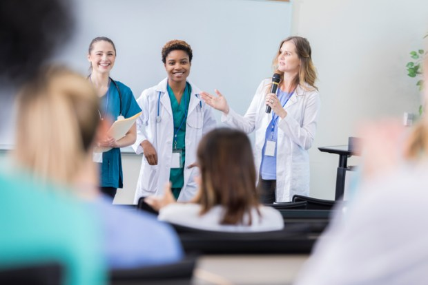 Confident diverse female healthcare professionals speak at a health seminar