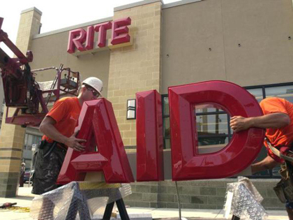 ** FILE ** Workers place half of a Rite Aid sign on sawhorse during sign installation at a new Rite Aid store in Philadelphia, Thursday, July 22, 2004. Rite Aid Corp. reported a second-quarter profit of $9.8 million on Thursday, Sept. 23, 2004, citing better cash flows and a reduction in inventory expenses. (AP Photo/Jacqueline Larma)