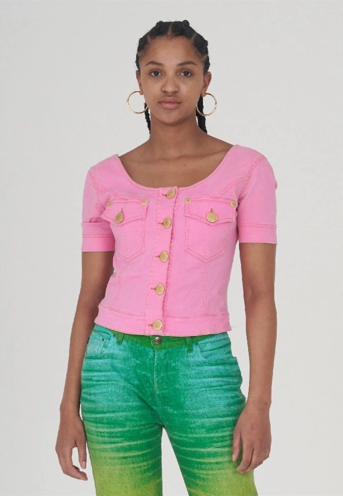 Woman wearing big hoop earrings in gold and a bright pink denim fitted top with green faded jeans.