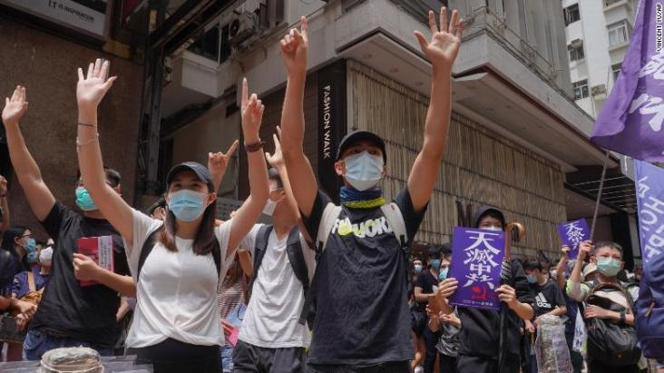 Protesters gesture with five fingers, signifying the