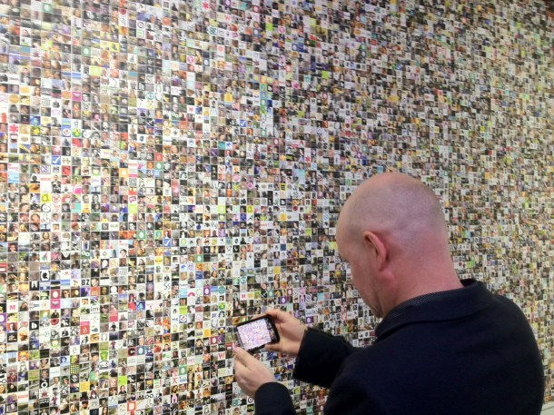 man photographing a wall of photo avatars and portraits