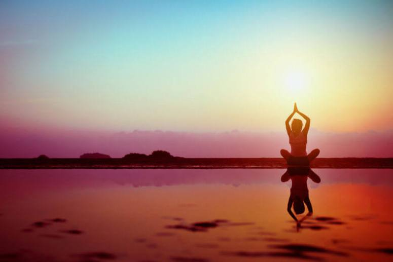 Silhouette of young woman practicing yoga on the beach at sunset
