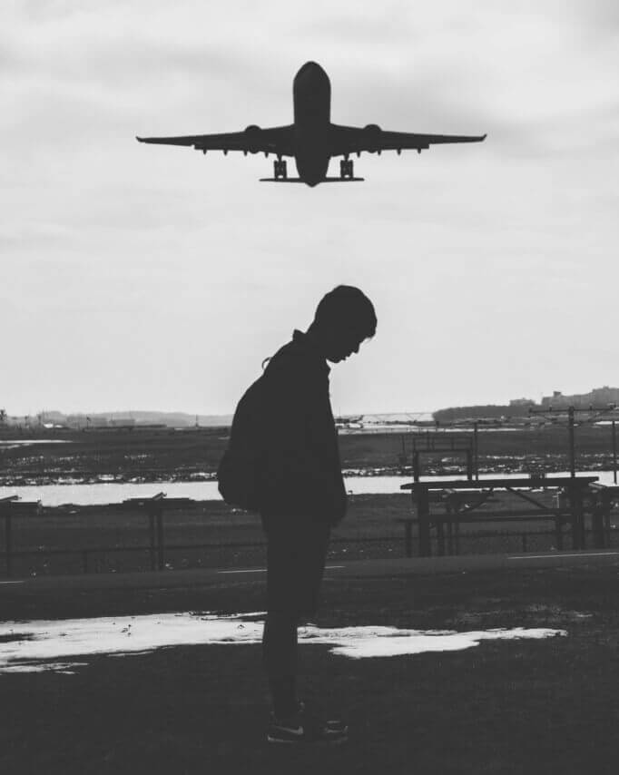 Plane flies over a sad man in a long distance relationship