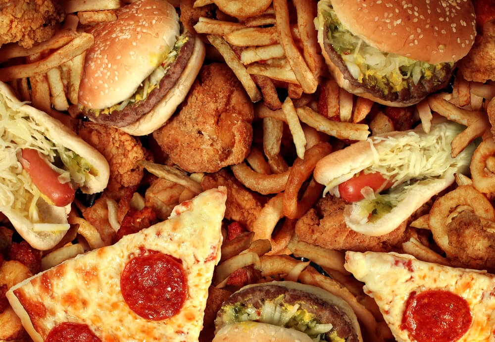 Fast food concept with greasy fried restaurant take out as onion rings burger and hot dogs with fried chicken french fries and pizza as a symbol of diet temptation resulting in unhealthy nutrition.