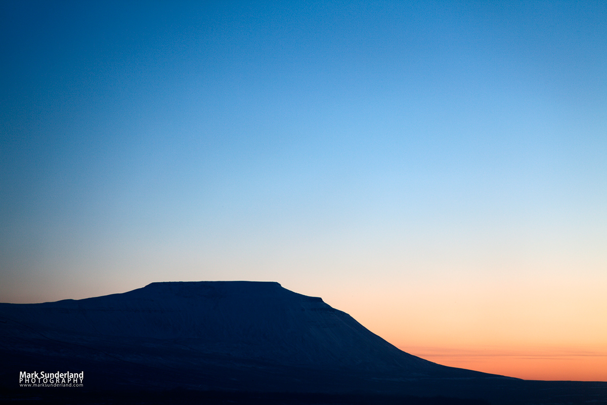 The flat topped peak of Ingleborough at Sunset in winter, Ribblehead, Yorkshire Dales