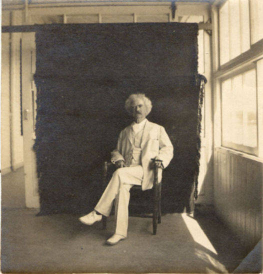 Samuel Clemens in white suit seated in front of a backdrop, ca 1909. Probably taken at Stormfield, Clemens' last home near Redding Connecticut.