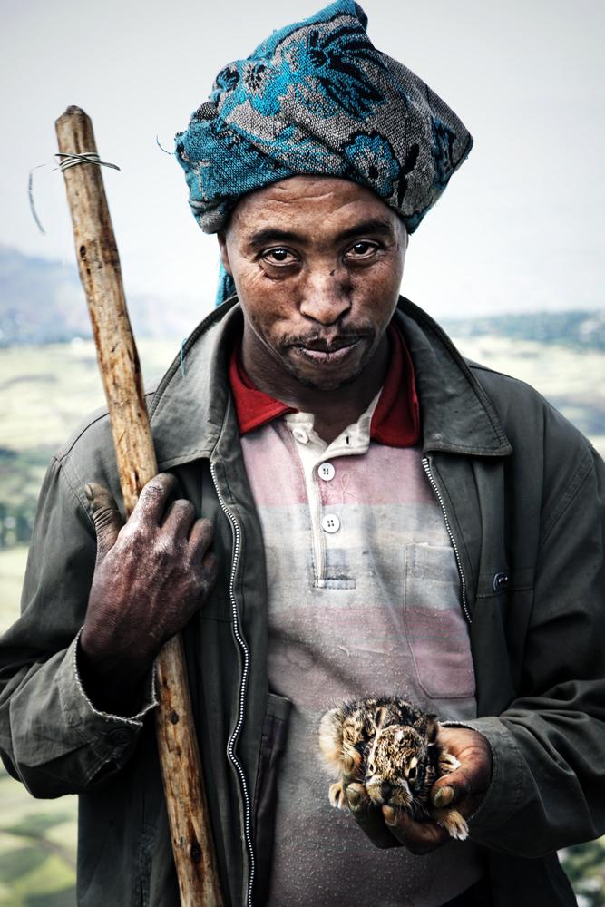 Ein Mann steht kurz hinter Addis Abeba am Straßenrand. In der Hand hält er einen kleinen Hasen.