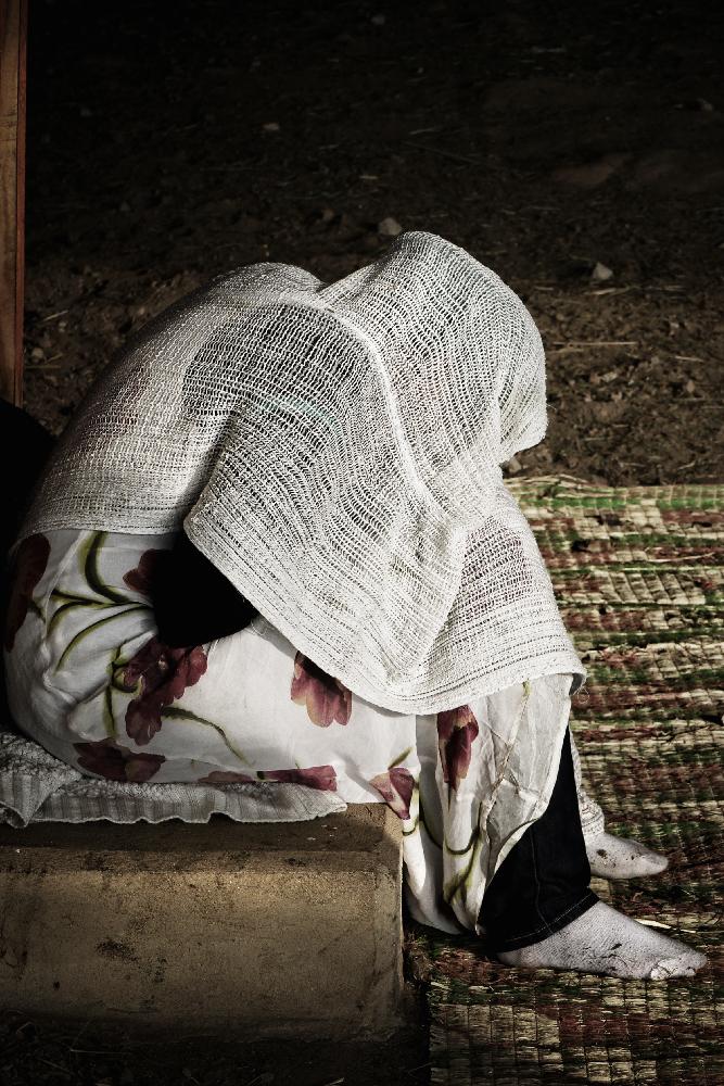 Eine Bettlerin hofft vor einer Kirche auf Almosen.