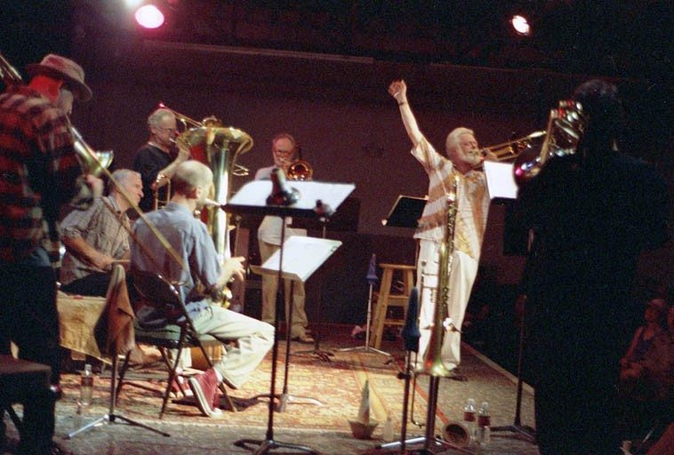"""Roswell Rudd & Bonefied -- May 22, 2000 at The Outpost Performance Space, Albuquerque -- Bonefied was a New Mexico five-trombone ensemble created by Steven Feld and on this occasion they debuted Roswell's extended work """"Cry of the Petroglyphs"""" that he had sketched out after a previous visit to New Mexico when I had drove him over to the west side of town and showed him some of the 17,000+ ancient (circa 2000BP - 1300AD) petroglyphs --- Left to Right: J.A. Deane (trombone), Jefferson Voohees (drumset), Gary Sherman (trombones), Mark Weaver (tuba & trombone), Kurt Heyl (trombone), Roswell Rudd (conductor), and from the rear: Steve Feld (trombone) -- photograph by Mark Weber"""