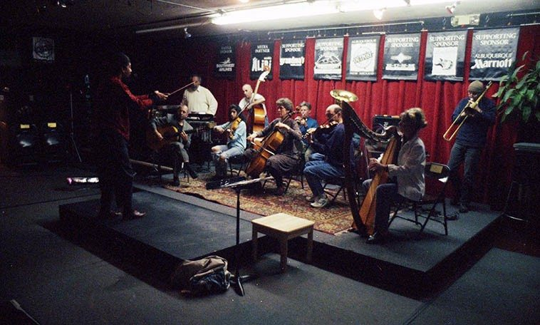 Butch Morris rehearsal for Conduction 101 -- April 8, 1998 at Outpost Performance Space (when it was located at 112 Morningside) Albuquerque -- photo by Mark Weber: Butch Morris, conducting; Stefan Dill, guitar; Ken Battat, percussion/vibes; David Parlato, bass; Alicia Ultan, viola; Katie Harlow, cello; Jonathan Baldwin, cornet; Tim Zannes, violin; Courtney Smith, harp; J.A. Deane, trombone/electronics