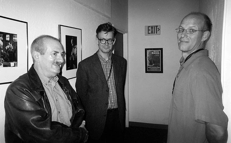 """Kenny Davern, Ab Baars, Michael Moore in the hallway at Outpost Performance Space -- There's a real story behind this: Kenny & Elsa lived in the eastern mountains outside Albuquerque, and on this evening (October 25, 2oo4) Kenny and I were on the telephone but I had to get over to Outpost and I said to KD, """"Man, if you got any sense you'd make this concert because these guys are so far out that they're back in, one of the great bands on the planet"""" and I didn't actually expect Kenny to come, but about 15 minutes into ICP's first set in the door comes Kenny, and I groaned to myself, man, I hope Kenny likes this madness or he's going to kill me ------ Well, at the break he comes over to me with eyes sparkling and wildly says, """"THESE GUYS ARE GREAT!"""" And I looked at him wondering what he had been smoking? They of course WERE great, but Kenny was somewhat a traditionalist, even though he is on record as approving of Ornette at the 5 Spot 1959 (his published letter to dOWNBEAT at the time) and also dug Albert Ayler, but he could be pretty tough on much else in the avant garde. SO, I take him backstage and introduce him, and everybody's happy, and Kenny even pointed to Han's rolled up pant's cuff and said """"Cliff Leeman"""" and Han jumped out of his chair with glee because he knew what Kenny was talking about (Eddie Condon's drummer Cliff Leeman did the same thing with his cuff), and so the librarians in the band were flipping through their book and pulled all the old Duke, Hoagy, Louis, 1930s things they had and the entire second set was for Kenny, and Kenny just fell in love ------- afterwards, as they were packing Kenny says to them like a kid who wants to join the circus: """"Take me with you"""" ----------AND SO THEY did: on their subsequent annual return to Albuquerque the next year (2005) Kenny played the entire show in the reed section. AND THAT's another story, pure glory, luckily we have it recorded . . . . . . ."""