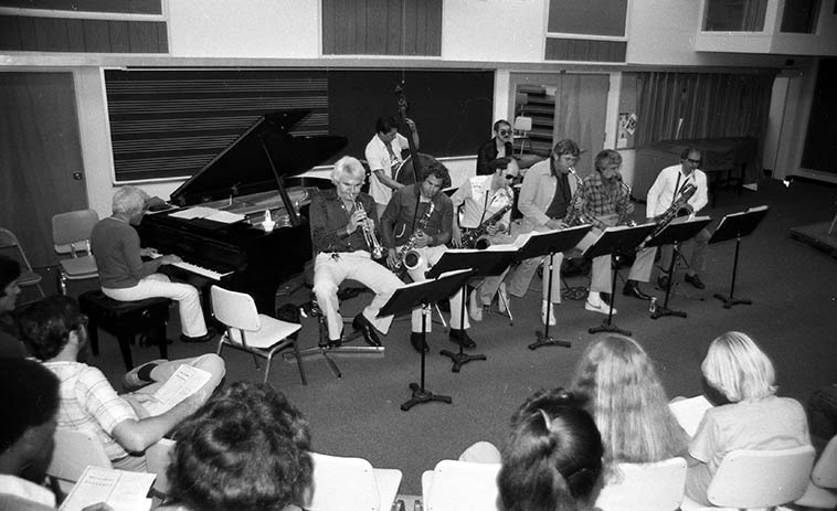 Supersax, the band that played Bird: Lou Levy, piano; Frank DeLaRosa, bass; John Dentz, drums; Conte Candoli, trumpet; Jay Migliori, Ray Reed, Med Flory, Lanny Morgan, Jack Nimitz, saxophones ---- Clinic at Cal Poly, Pomona, California -- June 6, 1980 -- photo by Mark Weber ------ These guys were uniquely suited to play Bird simply because he was their idol and they had grown up as youngsters absorbing Bird and were hardcore boppers ---- also, they could read this involved material because they had all spent time in the big bands of Kenton, Woody Herman, Maynard Ferguson, et. el. ------ By the time Med sat down in the early 70s to finally bring this idea to fruition and write some charts he had been in big bands 25 years ( ! ) SO, he KNEW what he wanted to hear ------ I wrote one of my most extensive ethnographies on this band SUPERSAX back before we stared Jazz For Mostly, so you can find it at drummer Cal Haines' website ---- Supersax recorded eleven albums of pure majesty and utter virtuosic artistry