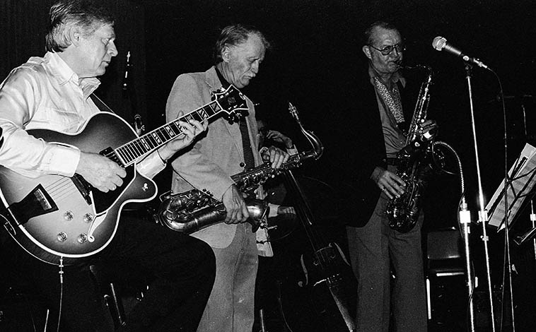 Mundell Lowe (guitar), Bill Perkins (tenor), Luther Hughes (bass), Bob Cooper (tenor) --October 9, 1982 at Los Angeles Press Club -- photo by Mark Weber ---- Note the plexiglass reflector mounted on bell of Perk's tenor, he made that himself