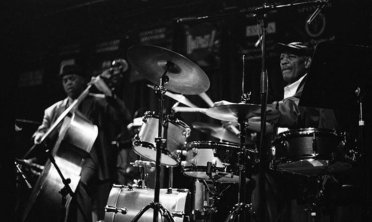 Victor Lewis using two snare drums w/ George Cables Trio (Essiet Essiet on the Outpost bass) -- November 21, 2o15 -- photo by Mark Weber -- Victor probably brought his own cymbals and maybe that extra snare (using two snares is not a regular occurrence with his music)