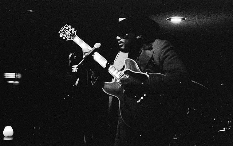 """Otis Rush in a little dive on the Near North Side of Chicago -- December 10, 1988 -- photo by Mark Weber -- and it was COLD in Chicago that week -- Otis Rush is one of the baadest of the baad for post-war Chicago blues guitar -- and this little club only had about a dozen other people there that night, so, we had him all to ourselves ----- There's a convention in rhythm & blues showbiz where the backing band comes out first and plays 3 or 4 numbers to """"warm up the audience"""" ----- well, this band was so killin' I didn't care of Otis ever came out, gawd, Chicago was so full of great bluesmen those years (Dave Cook, organ; Sam Burton, drums; James Wheeler, guitar, Emmett Sutton, bass) ----- While Otis was playing I somewhat loudly was explaining to Janet (I'd had a few maybe too many beers) how Otis can arpeggiate a chord and then inexplicably bend all the strings in opposite directions which makes for a very wobbly out-of-kilter sound ---- Well, he heard me, and walked over to our table and stuck his guitar neck right in front of Janet and while the band was burning full on, he demonstrated this technique, articulating that chord over & over, in time with the blues they were scorching the place with -- club Close Encounters, 936 N. Rush Street"""