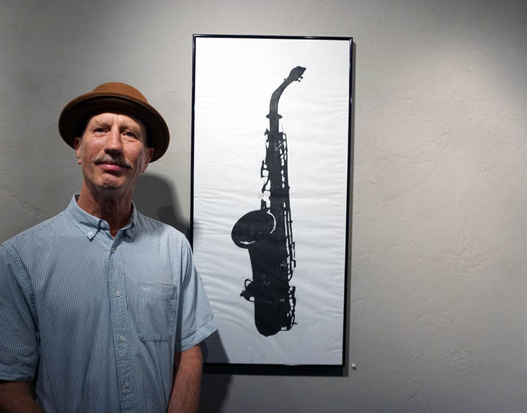"Mark Weaver and his woodblock print on rice paper ""Greg's C Melody Saxophone""(1983) as part of Inpost Artspace group show Musicians Making Art now showing at Outpost Performance Space – photo by Mark Weber – July 15, 2o18 Albuquerque (Mark Weaver is a tuba maestro who recently performed with Joseph Daley Trio on a little tour of New Mexico)"