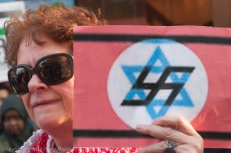 Woman holds sign showing Star of David overlaid with swastika in Palestine Land Day protest opposite Israeli Embassy in solidarity with the Global March to Jerusalem