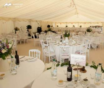 Interior wedding marquee staged for wedding and guests with cream accents and chandeliers