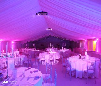 Image of white linens, white banquet chairs, pink lighting, and ceiling swags