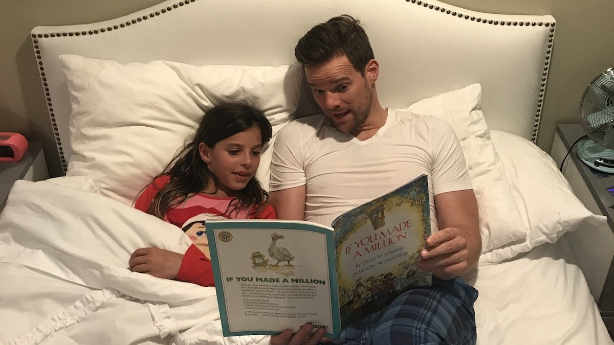 Father and daughter reading books about money