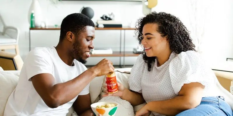 couple eating on couch