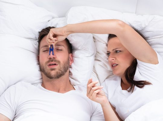 Image of a couple laying in bed frustrated