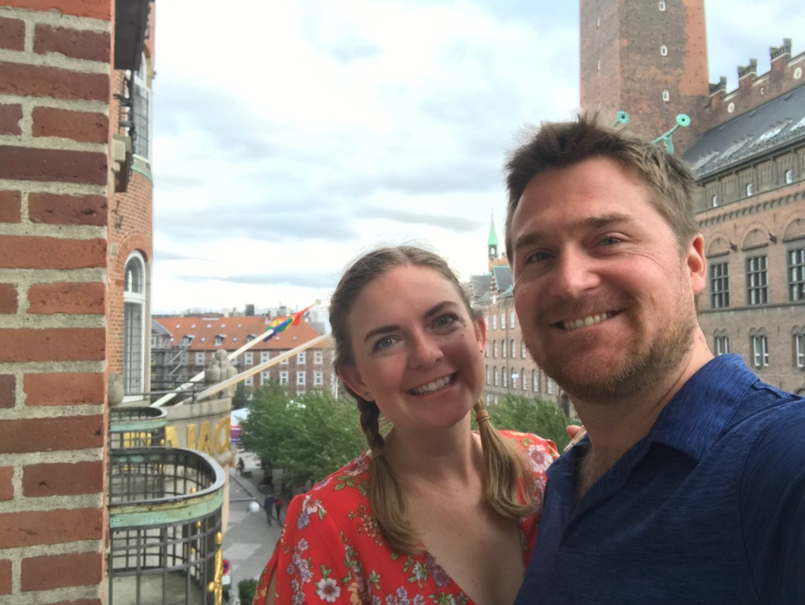 Last Day of Vacation in Copenhagen, Denmark. Tim and Kara pose for a selfie of a building balcony above the street below.