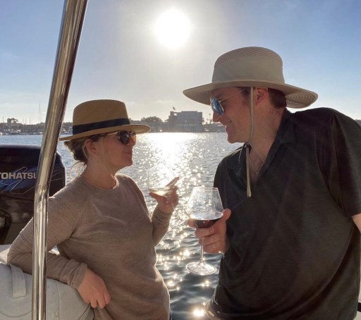 The Married Explorers, Tim and Kara, enjoying the sunset on their rental house boat in Newport, California while they travel.