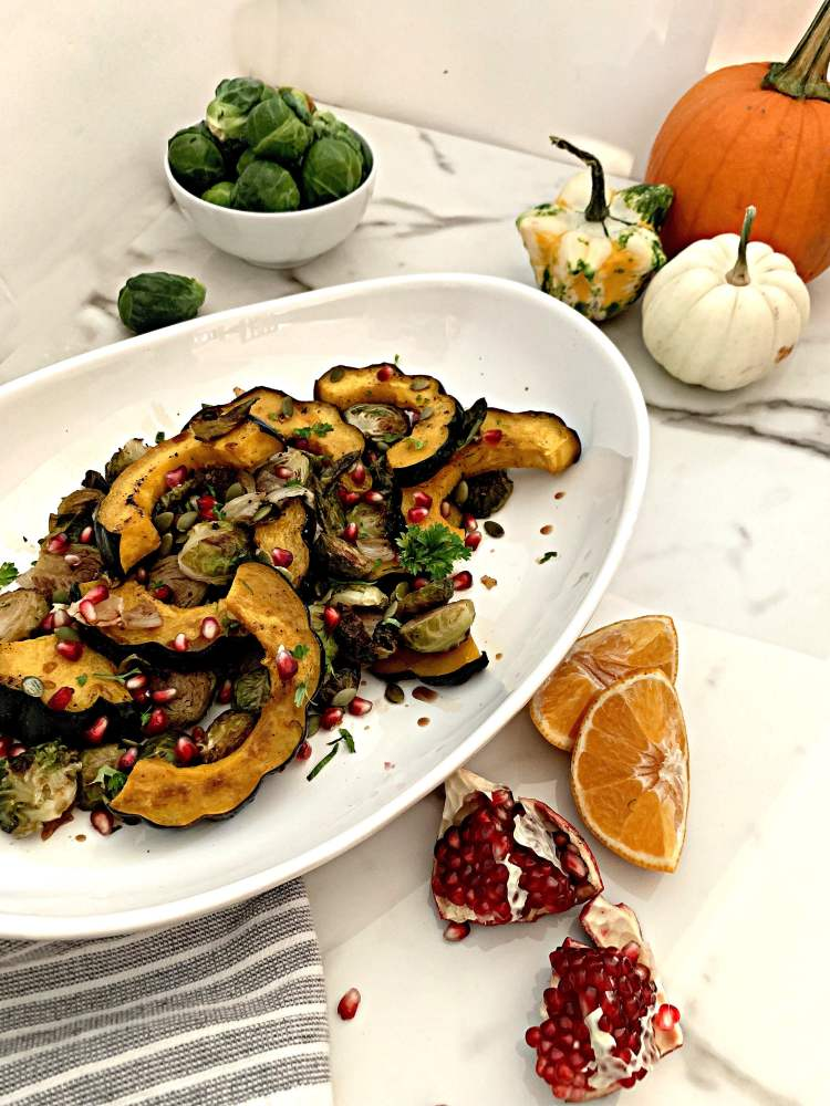 Maple Balsamic Brussels Sprouts and Acorn Squash topped with pomegranate and pumpkin seeds on a white platter