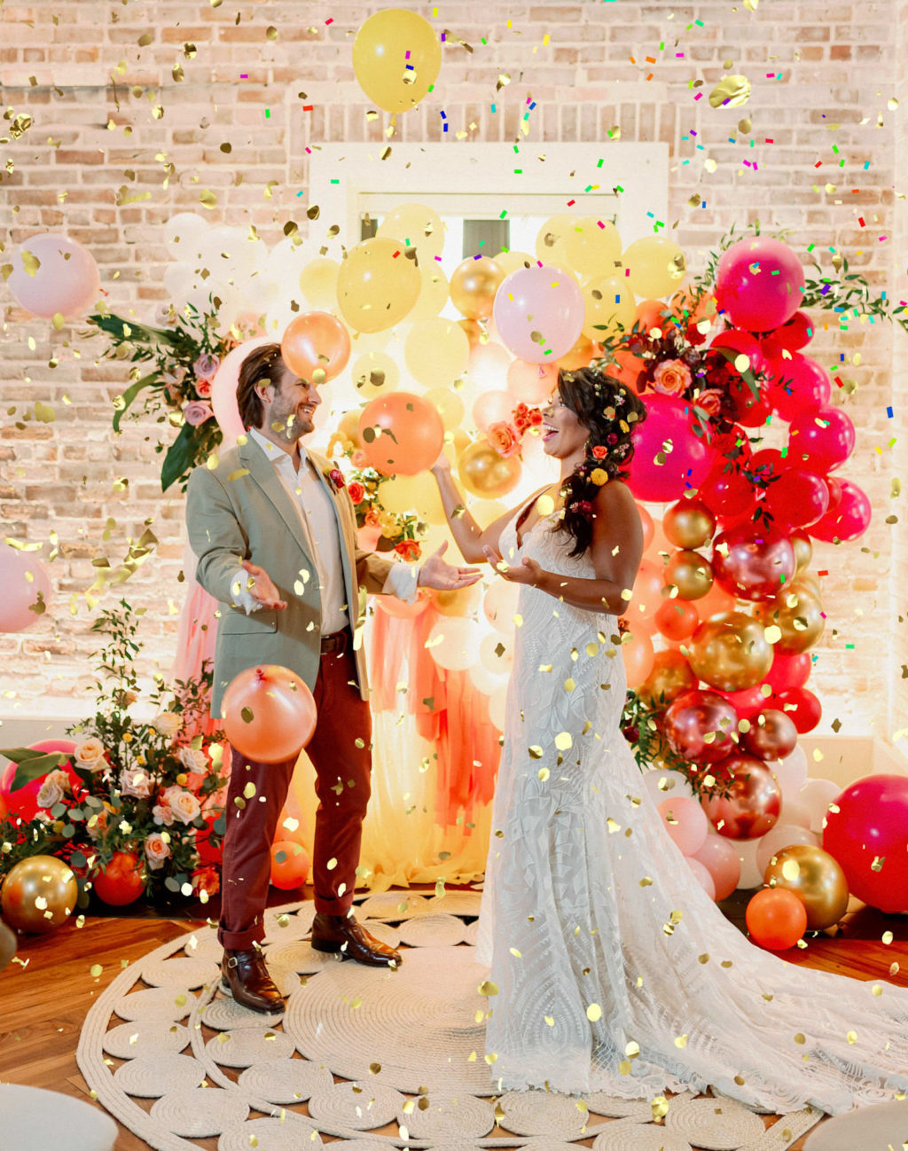 Whimsical and Colorful Bride and Groom Gold Confetti Photo with Orange, Pink, Yellow and Gold Balloon and Fringe Ceremony Backdrop   Tampa Bay Wedding Photographer Dewitt for Love   St. Pete Modern Industrial Wedding Venue Red Mesa Events