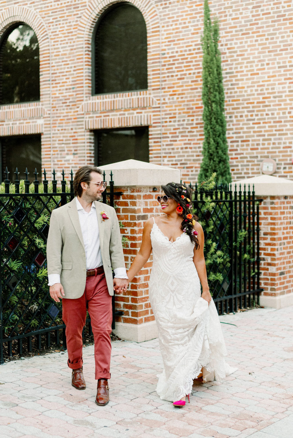 Whimsical Bride Wearing Lace Boho Spaghetti Strap and V Neckline Wedding Dress, Hair in Braid with Colorful Flowers and Sunglasses, Groom in Dusty Red Pants, Gray Suit Jacket and Red Retro Sunglasses   Tampa Bay Wedding Photographer Dewitt for Love   St. Pete Modern Industrial Wedding Venue Red Mesa Events