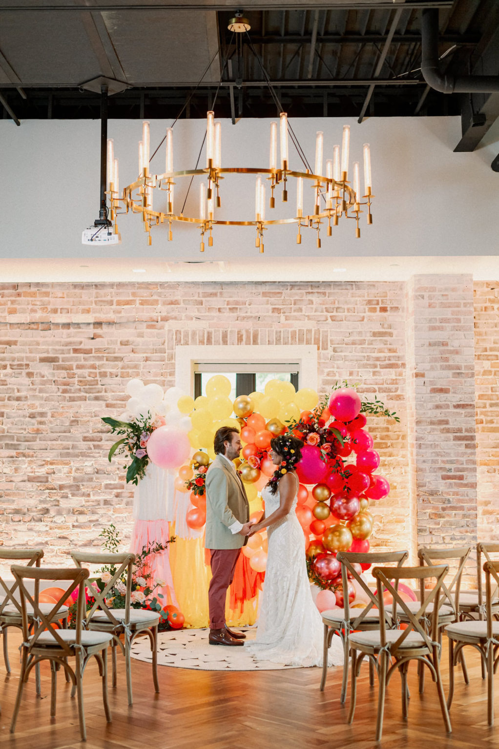 Bride and Groom Exchanging Wedding Vows, Whimsical and Colorful Wedding Decor, Yellow, Pink, Orange, White, Gold Fringe and Balloon Ceremony Backdrop, Wooden Cross Back Chairs, Gold and Candlestick Chandelier, White Brick Wall   Tampa Bay Wedding Photographer Dewitt for Love   St. Pete Modern Industrial Wedding Venue Red Mesa Events   Wedding Chair Rentals Kate Ryan Event Rentals