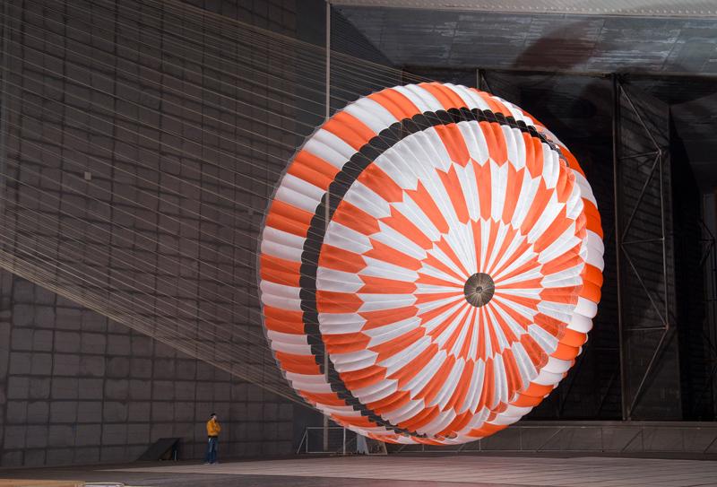 Il paracadute Mars 2020 largo 70 piedi, arancione e bianco, galleggia completamente gonfiato in un'enorme galleria del vento, facendo impallidire un ingegnere nelle vicinanze.