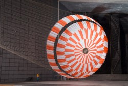 幅70フィートのオレンジと白の火星2020パラシュートは、巨大な風洞で完全に膨らんで浮かんでおり、近くのエンジニアを矮小化しています。