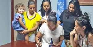 Signing off on the new UNDP grant were, KIO Club President Emma Kabua-Tibon, left, and UNDP Small Grants Manager Yoshiko Yamaguchi-Capelle. Standing from left: Monique Graham with daughter Iia, Shamanda Hanerg, and Francyne Wase-Jacklick.