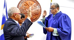 Enewetak Senator Jack Ading (left) takes the oath of office as the new Minister of Justice, Immigration and Labor from Chief Justice Carl Ingram as Ading's wife Luren holds the Bible. Photo: Hilary Hosia.