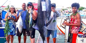 """Team Dragon, captained by Rudy Aliven (standing next to marlin, right), """"caught five"""" fish species to win the Catch Five carry over prize from a previous tournament during Friday's first day of fishing in the 36th annual Marshalls Billfish Club July tournament. Photo: Hilary Hosia."""