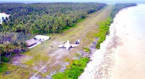 An Air Marshall Islands plane parked next to the airport terminal on Lae Atoll. Photo: Tyler Milne.