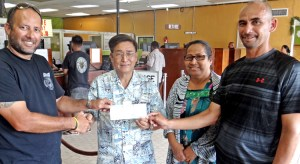 Marshall Islands Basketball Federation President Sherwood Tibon, left, and member at large Robert Pinho, right, accept a check from Bank of Marshall Islands President and CEO Patrick Chen and BOMI Executive Secretary Marilyn Harry for the BOMI 18th Ralik Ratak Shootout Basketball Tournament. BOMI is the major sponsor for the basketball showcase tourney. Photo: Hilary Hosia.