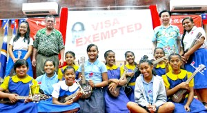 """Foreign Ministers John Silk of the RMI and Jaushieh Joseph Wu of ROC/Taiwan, left and right of """"visa waiver"""" banner, respectively, joined students from Assumption, Majuro Baptist Academy and Delap Elementary in celebration at the International Conference Center Tuesday. Photo: Hilary Hosia."""