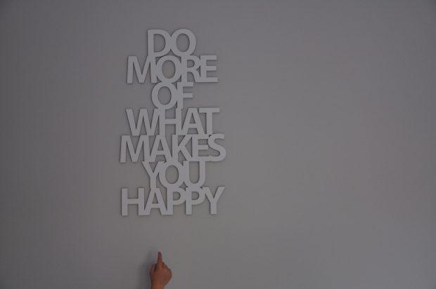 """Do more of what makes you happy"" hangt naast mijn bed."