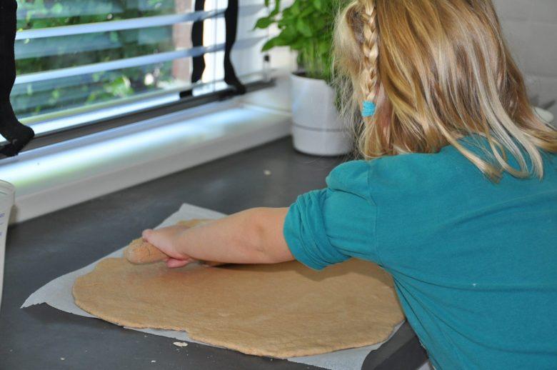 Dochterlief maakt een pizza, op de achtergrond zie je het kruidenpotje.